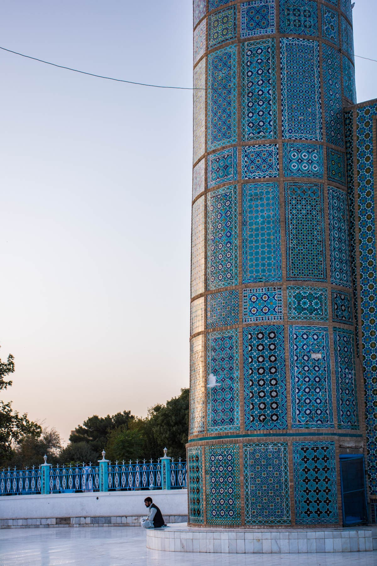 A man sitting contemplatively at the foot of a minaret of the Blue Mosque in Mazar-i-Sharif, Afghanistan, at sunset.