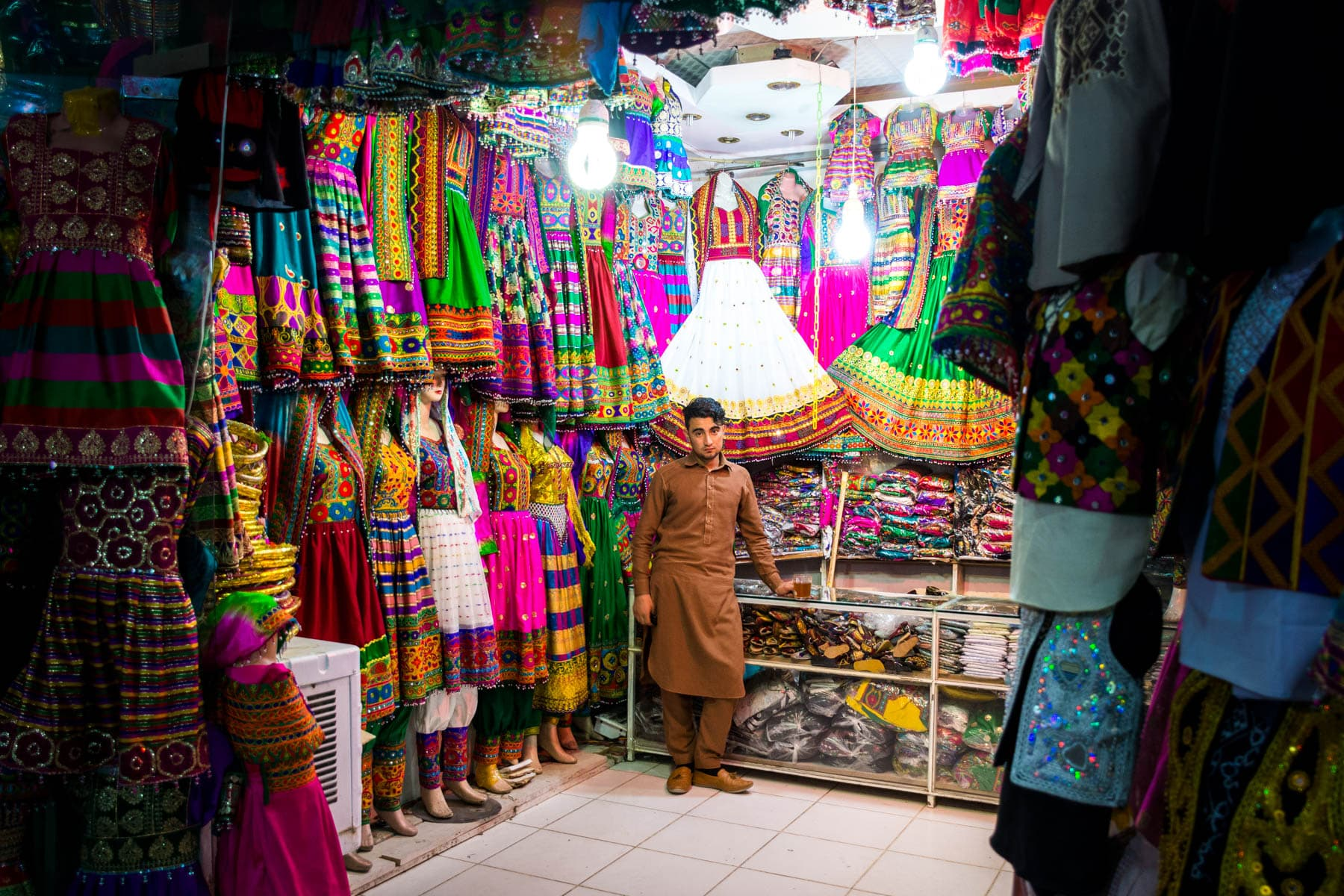 Photos of Mazar-i-Sharif, Afghanistan - A boy selling colorful women's clothes in a central bazaar - Lost With Purpose