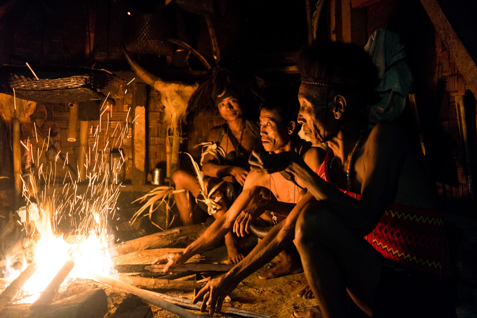 Snapshots of traditional tribal culture in Longwa village, Nagaland, Northeast India - Longwa men sitting around a fire - Lost With Purpose Travel Blog
