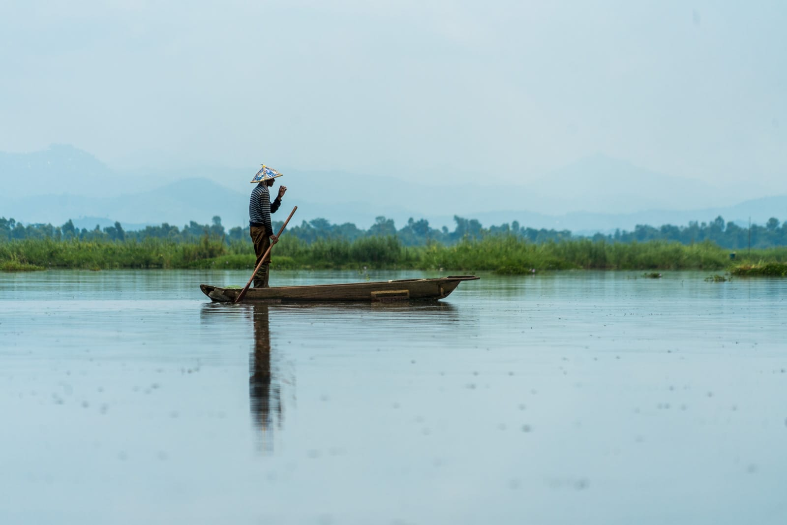 Why you need to visit Loktak Lake, Manipur, Northeast India - Fisherman standing in boat - Lost With Purpose