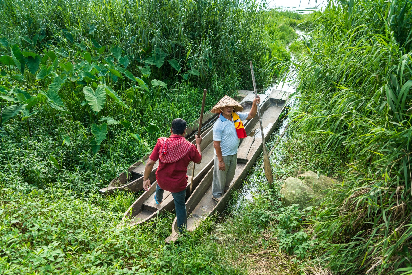 Why you need to visit Loktak Lake, Manipur, Northeast India - Two men climbing into wooden boats - Lost With Purpose