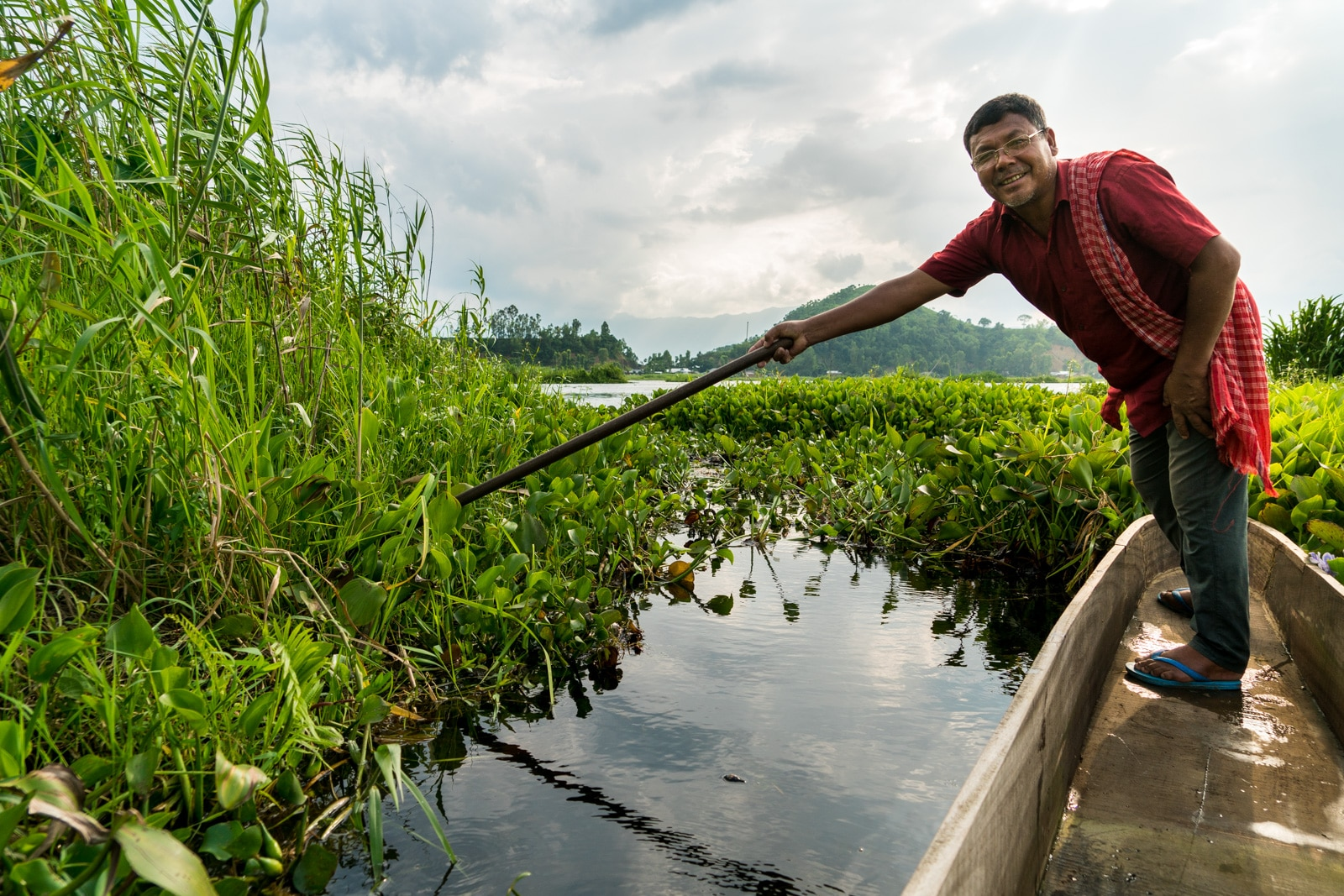Why you need to visit Loktak Lake, Manipur, Northeast India - Clearing a path through the phumdi on a boat ride in the lake - Lost With Purpose