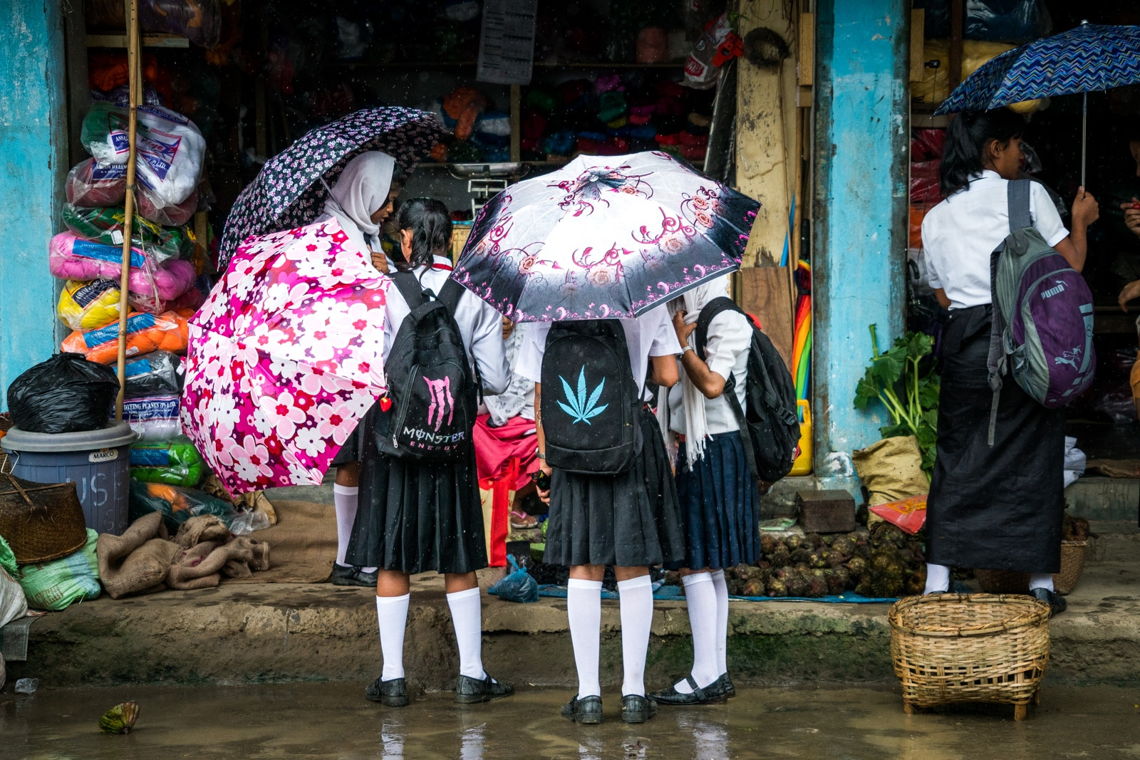 Monsoon travel packing list - Girls with umbrellas in Moirang, India - Lost With Purpose