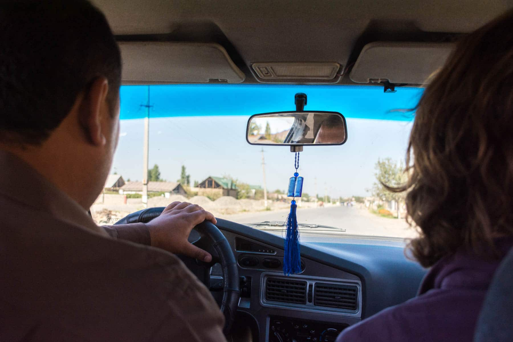 Two people sitting in a taxi on their way to the Uzbek - Afghan border