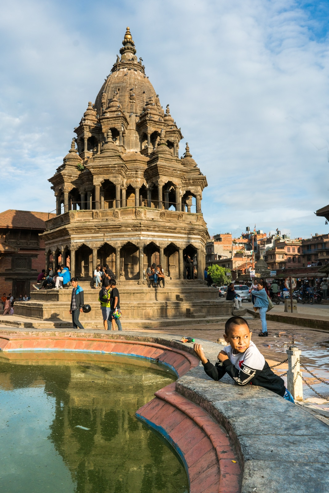 Devious young boy having an ice cream snack in the historic Durbar Square in Patan, Nepal.