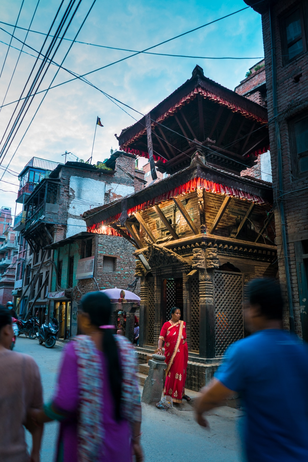 A local Nepali woman in a bright red sari before a small shrine on the busy streets of Patan, Nepal during twilight.
