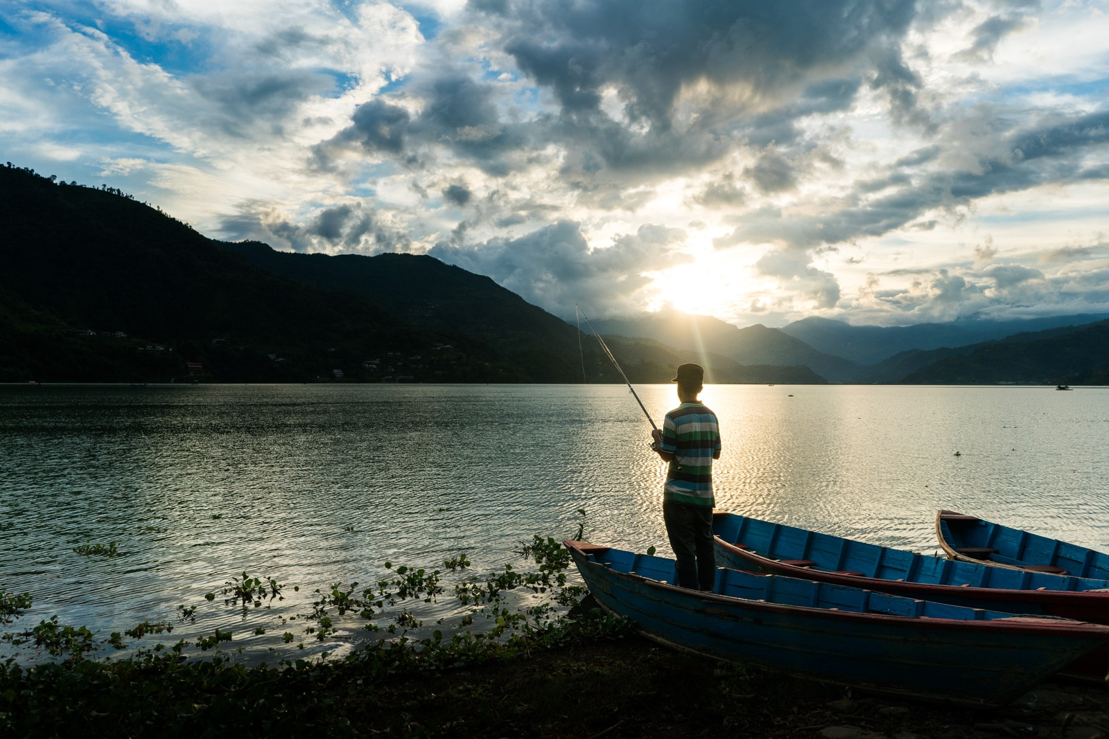 Travel in Nepal during monsoon - A boy fishing at Phewa Lake in Pokhara - Lost With Purpose travel blog