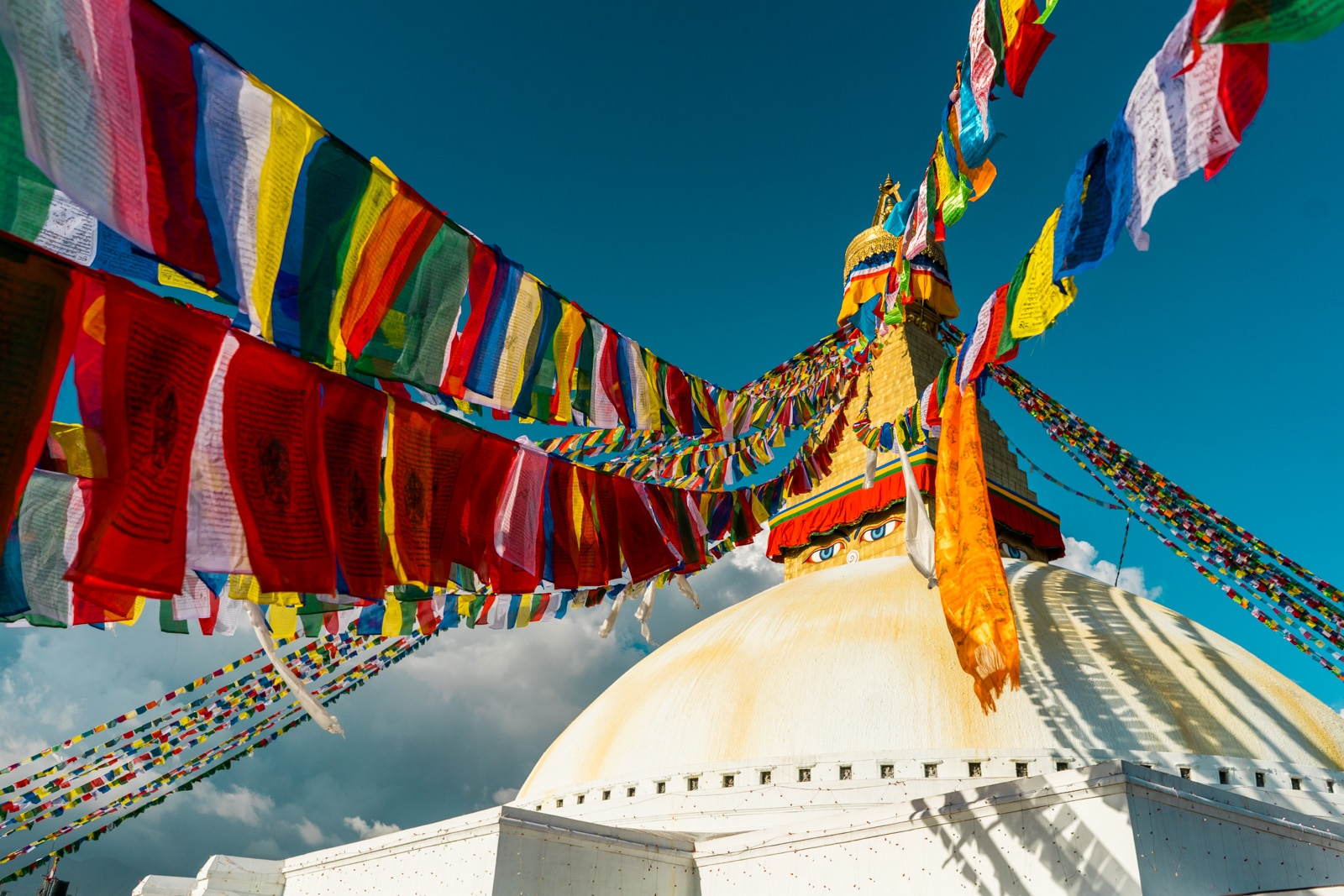 Traveling during monsoon in Nepal - Boudhanath stupa and prayer flags in the sun - Lost With Purpose travel blog