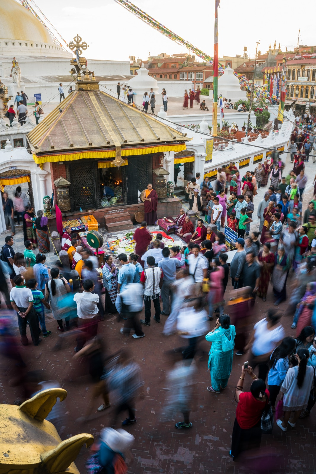 Rushing crowds of pilgrims and travelers visiting the famous UNESCO World Heritage site of Boudhanath stupa in Kathmandu, Nepal.