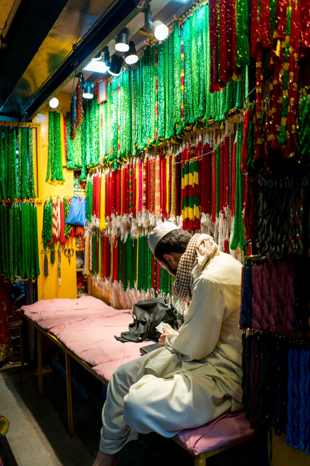 A man selling colorful jewelry in the New Market area of Kathmandu, Nepal.
