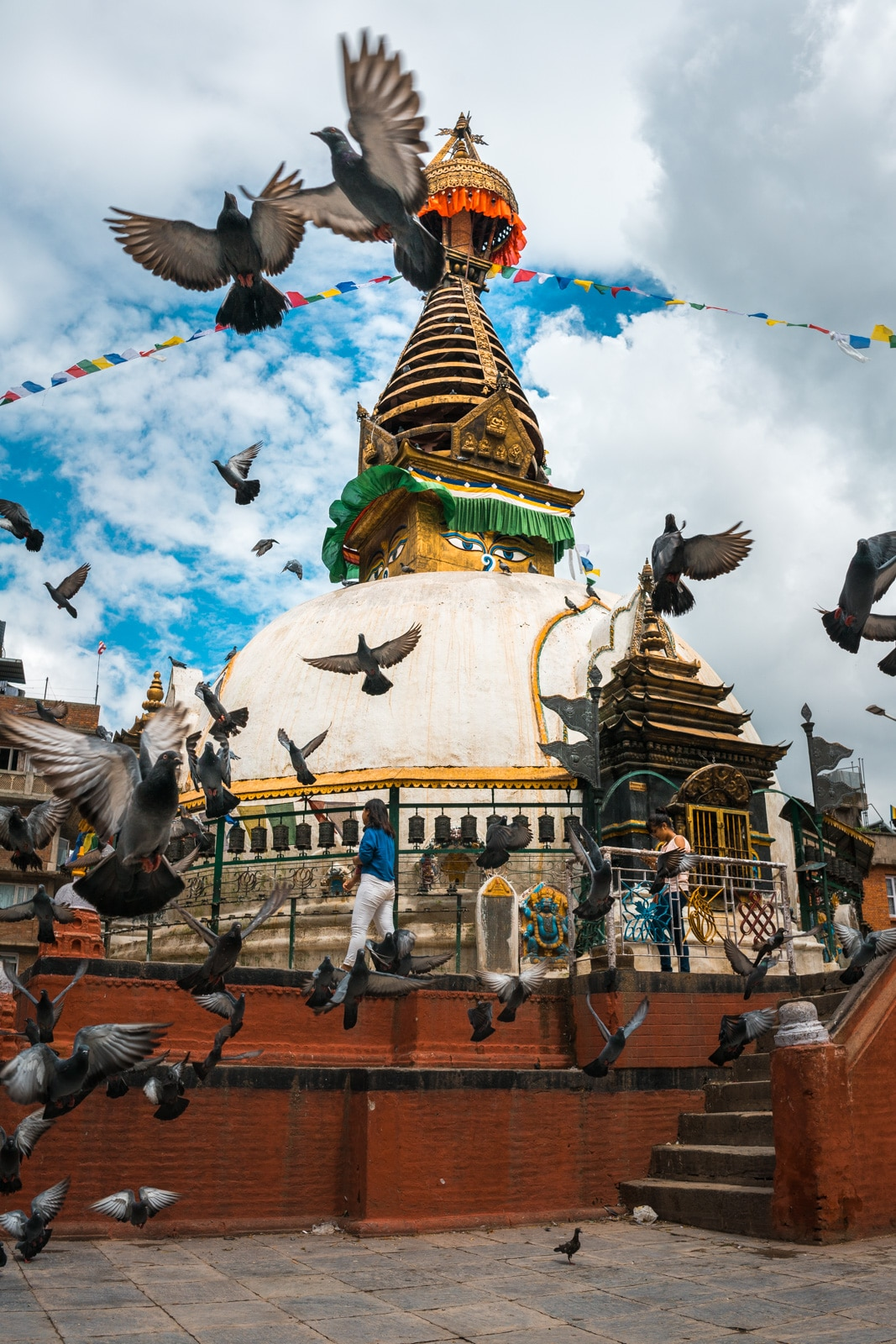 Flocks of birds flying before one of many scenic small stupas found throughout Kathmandu, Nepal.