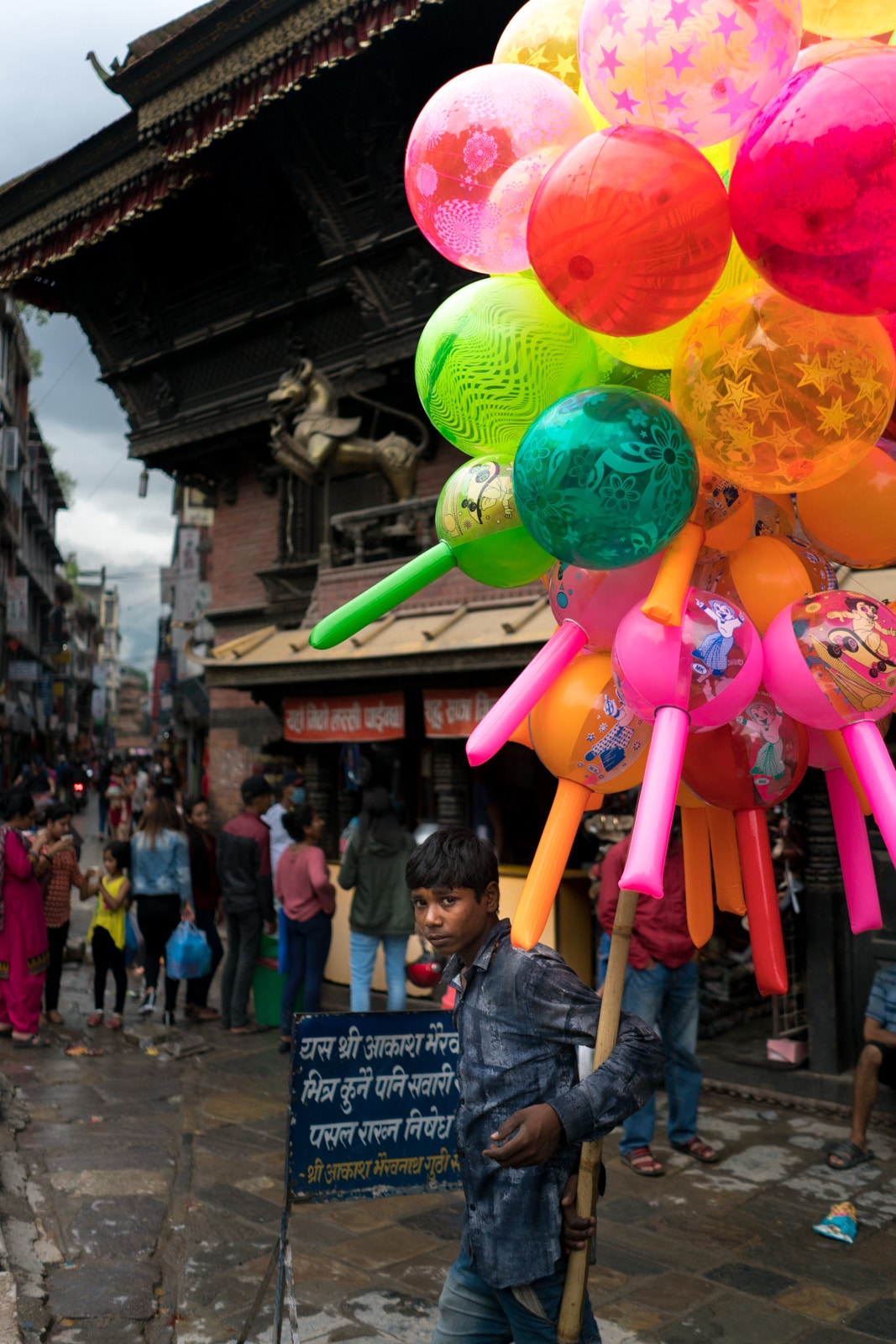 A young boy selling colorful balloons in a street market in Kathmandu, Nepal.
