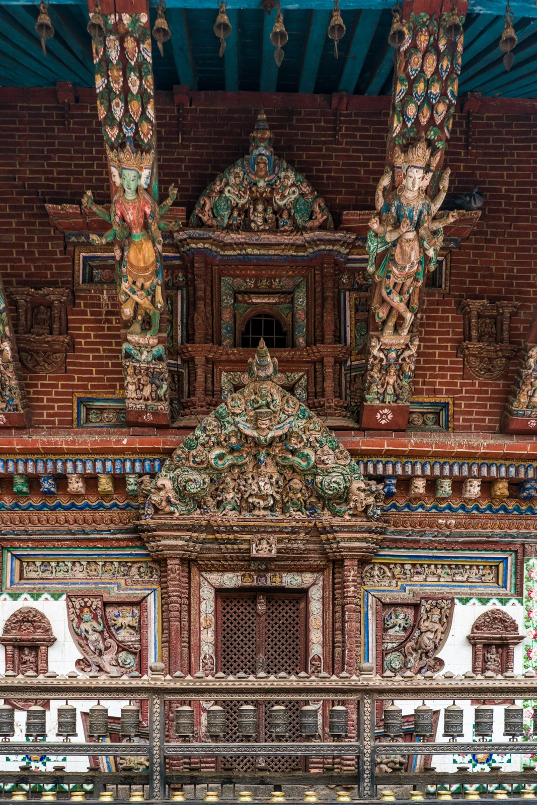 Intricate, painted wooden detail work on a red brick Buddhist stupa in the center of Patan, Nepal.