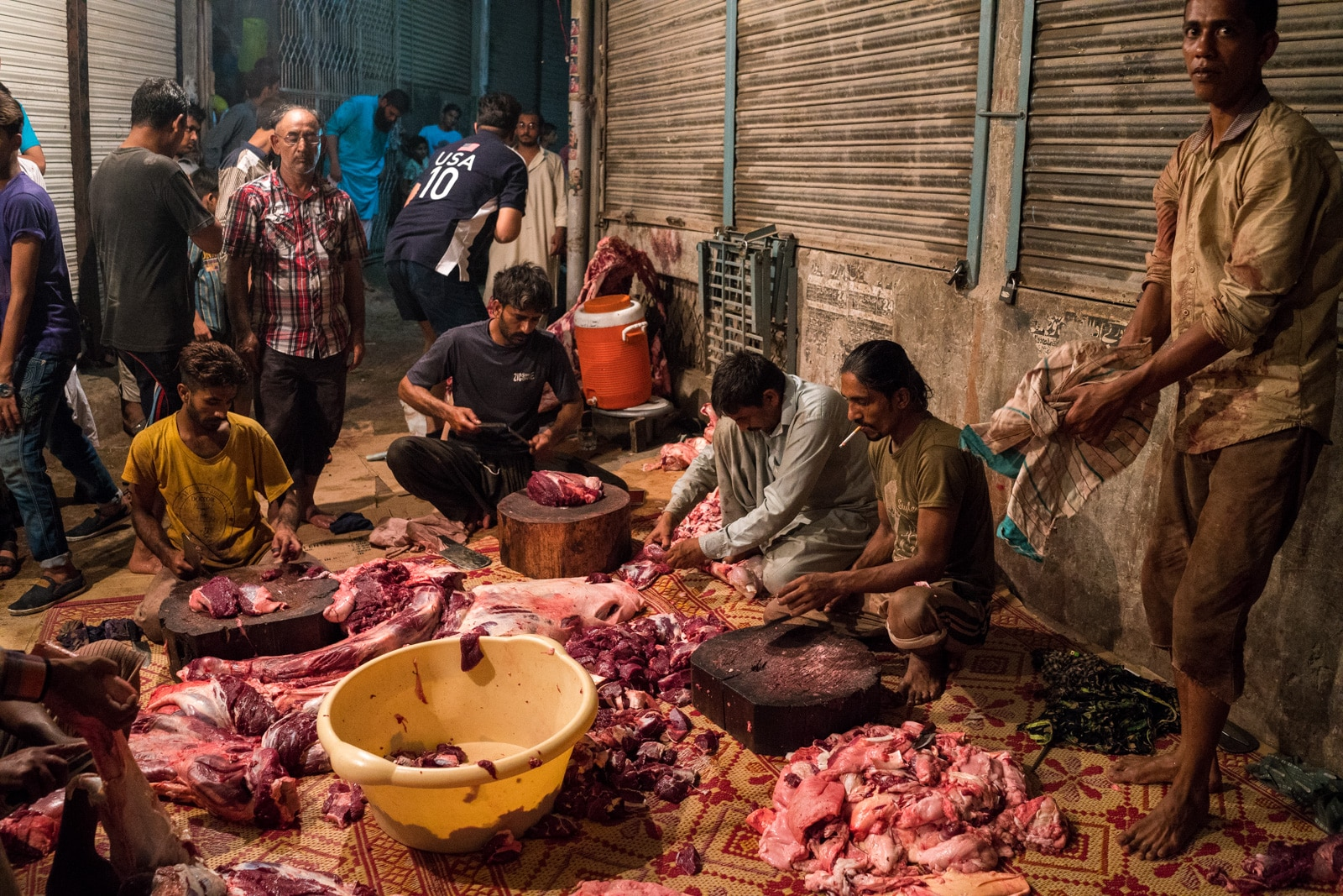 Celebrating Eid al-Adha in Lahore, Pakistan - Men chopping camel meat on the street - Lost With Purpose travel blog