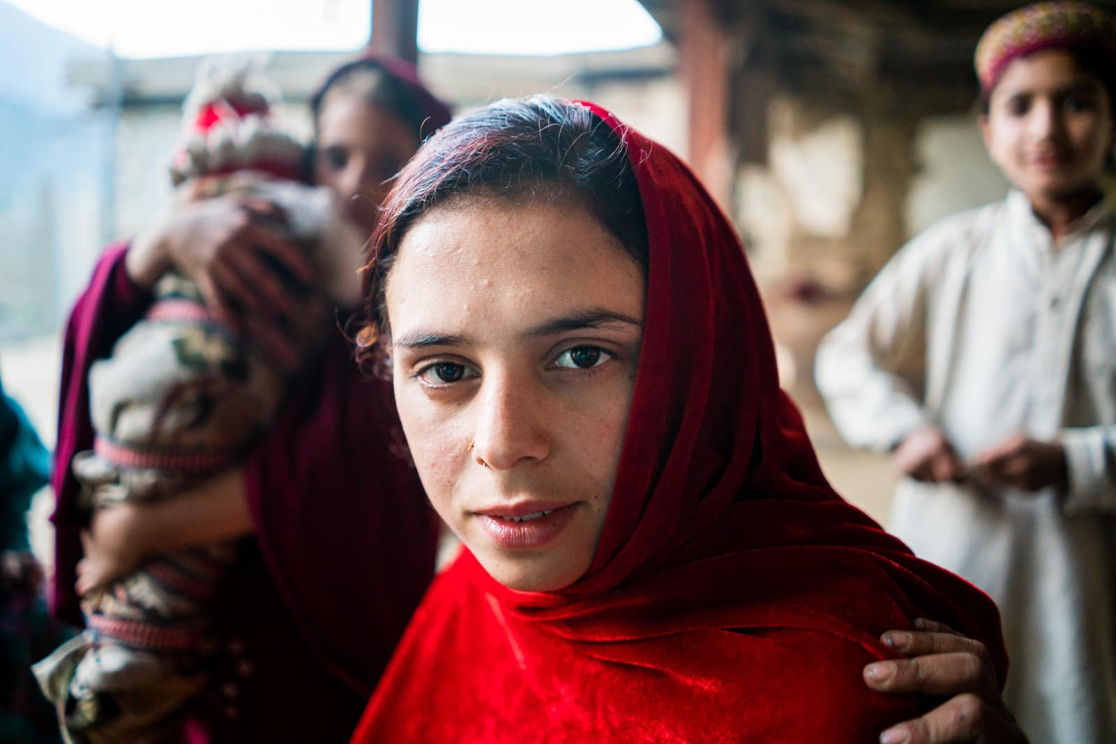 The great divide in Thall, Pakistan - Young girl in red hijab - Lost With Purpose travel blog