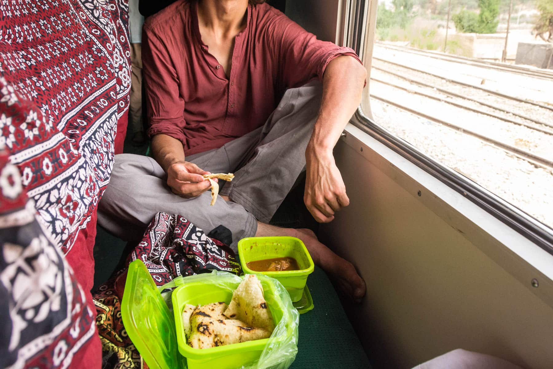 Guide to train travel in Pakistan - Eating a gift of food on the train - Lost With Purpose travel blog