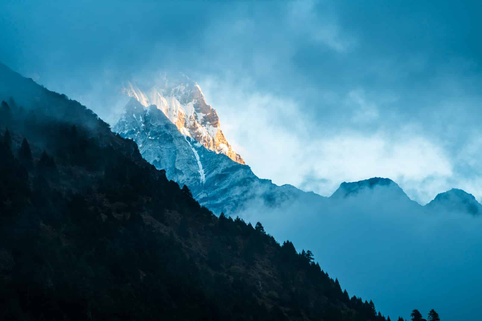 Guide to the Gasa - Laya trek in Bhutan - Mountain peeking through the clouds at sunrise - Lost With Purpose travel blog
