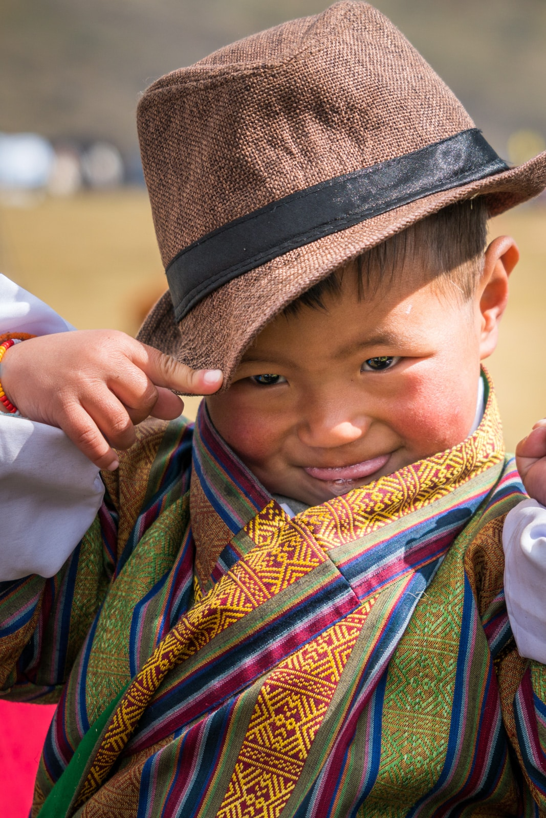 "An adorable young Bhutanese boy rocking a fedora and colorful ""gho"", traditional male Bhutanese dress, at the 2017 Royal Highlander Festival in Laya, Bhutan."