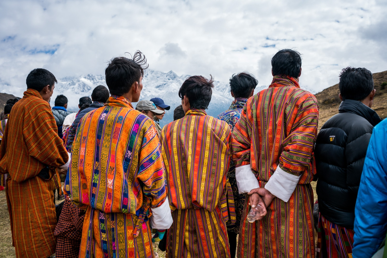 Photos of the 2017 Royal Highlander Festival in Bhutan - Men in colorful traditional Bhutanese gho watching the spectacle - Lost With Purpose travel blog