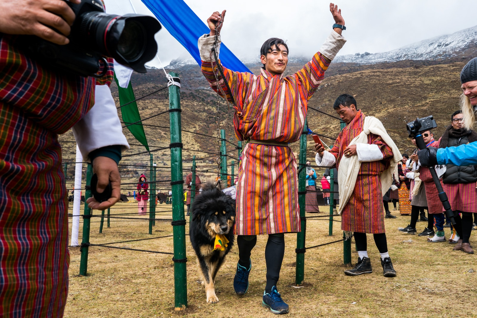 Photos of the 2017 Royal Highlander Festival in Laya, Bhutan - Man showing a prize winning Himalayan mastiff at the festival - Lost With Purpose travel blog