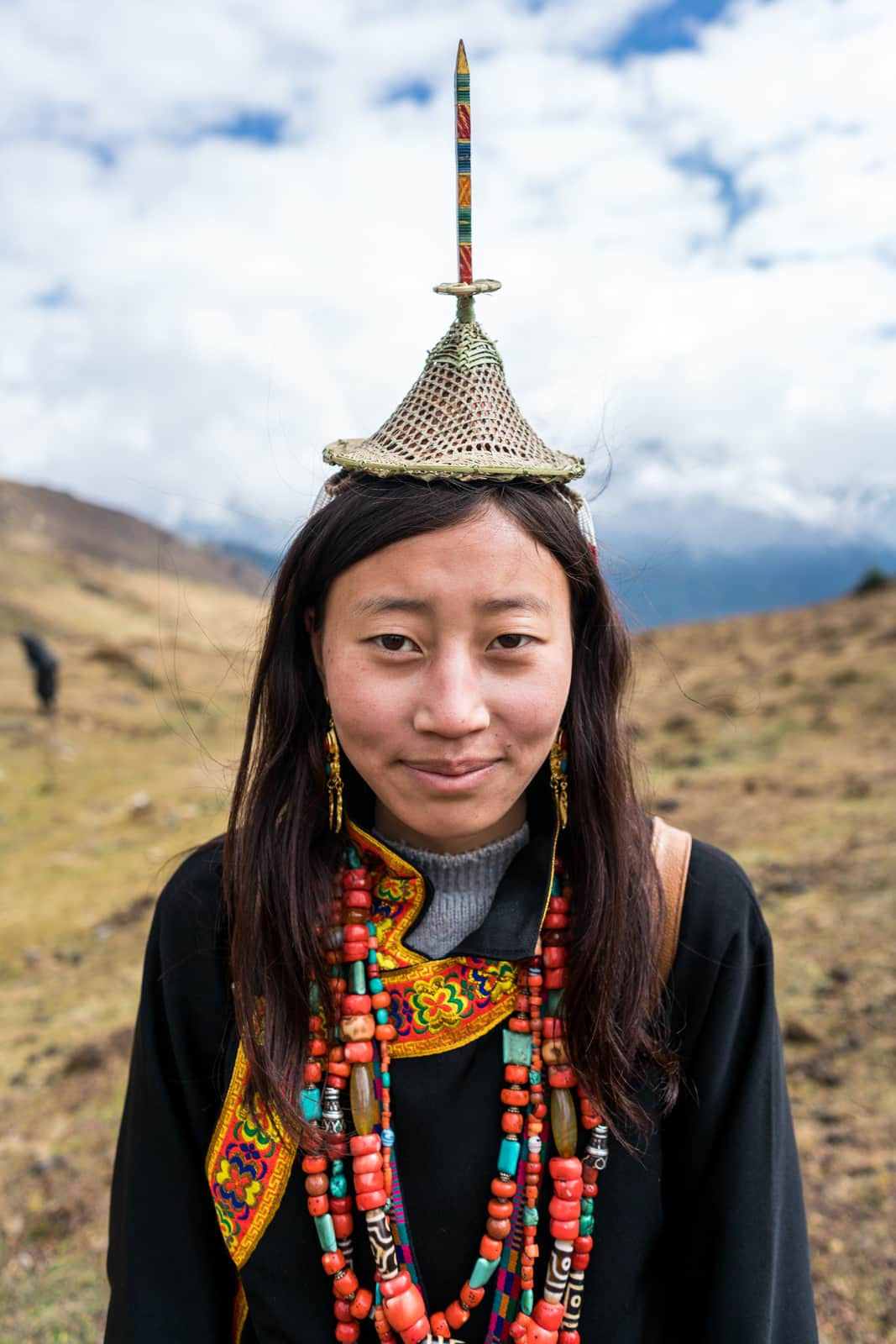 Portrait of a Layap girl in traditional headdress, dress, and beads at the 2017 Royal Highlander Festival in Laya, Bhutan. The perfect off the beaten track adventure in Bhutan!