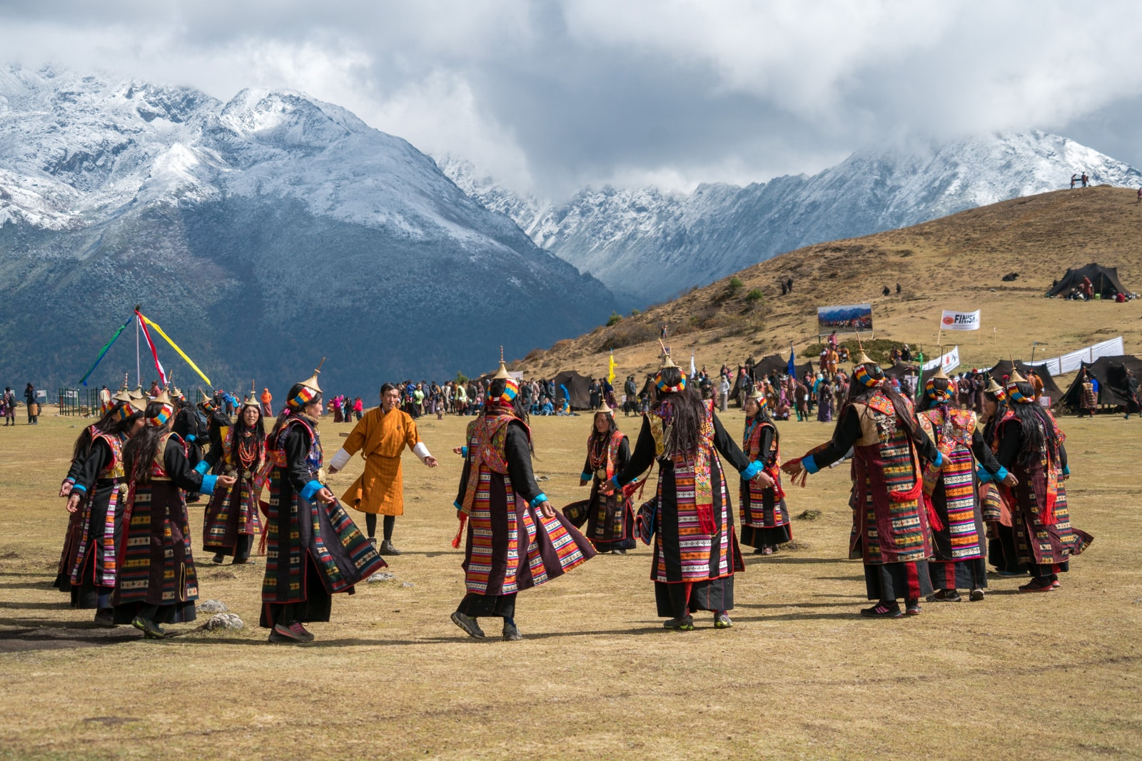 Photos of the 2017 Royal Highlander Festival in Bhutan - Women dancing in a circle at the festival - Lost With Purpose travel blog