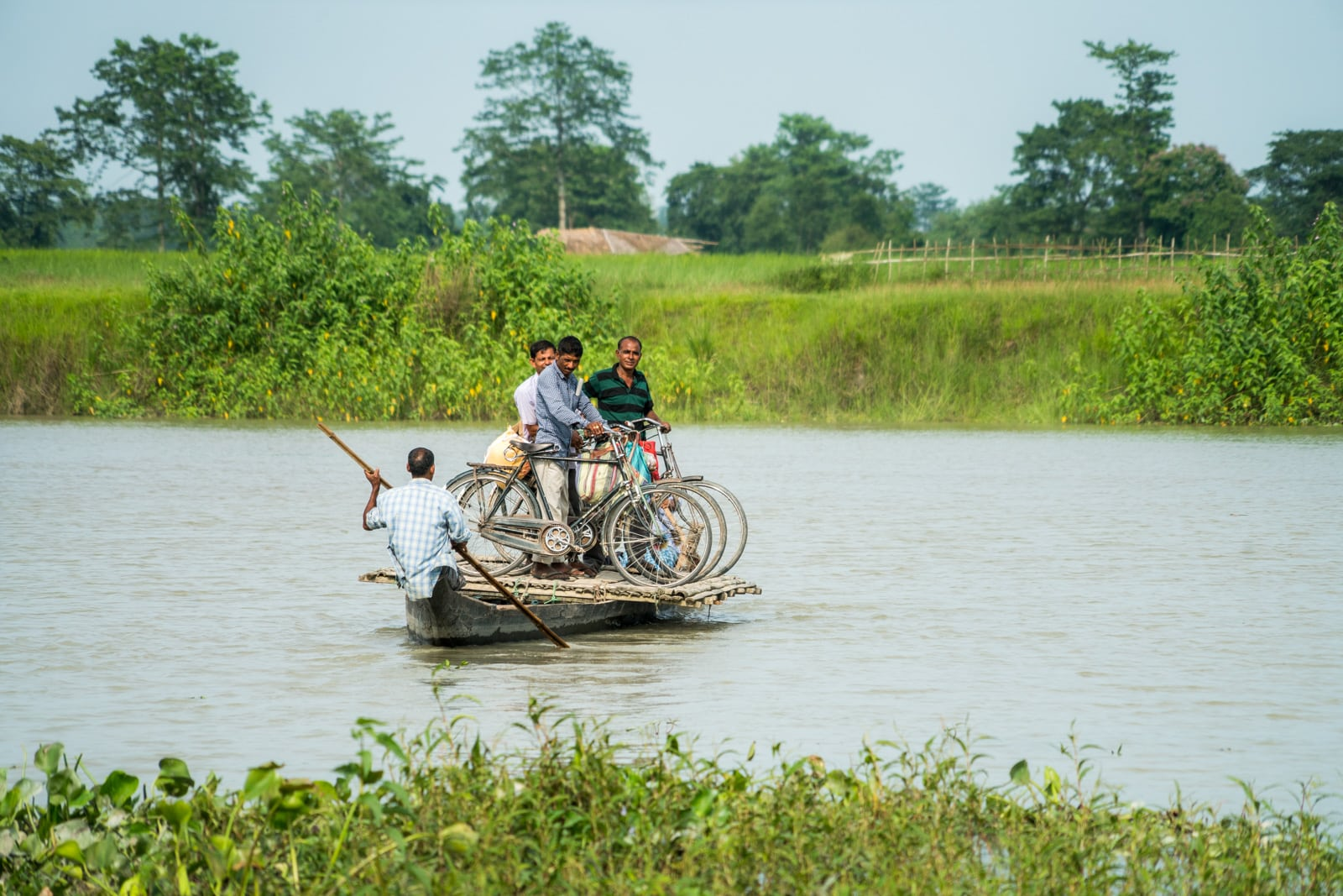 Men standing on a small ferry for cyclists in Majuli river island in Assam, India