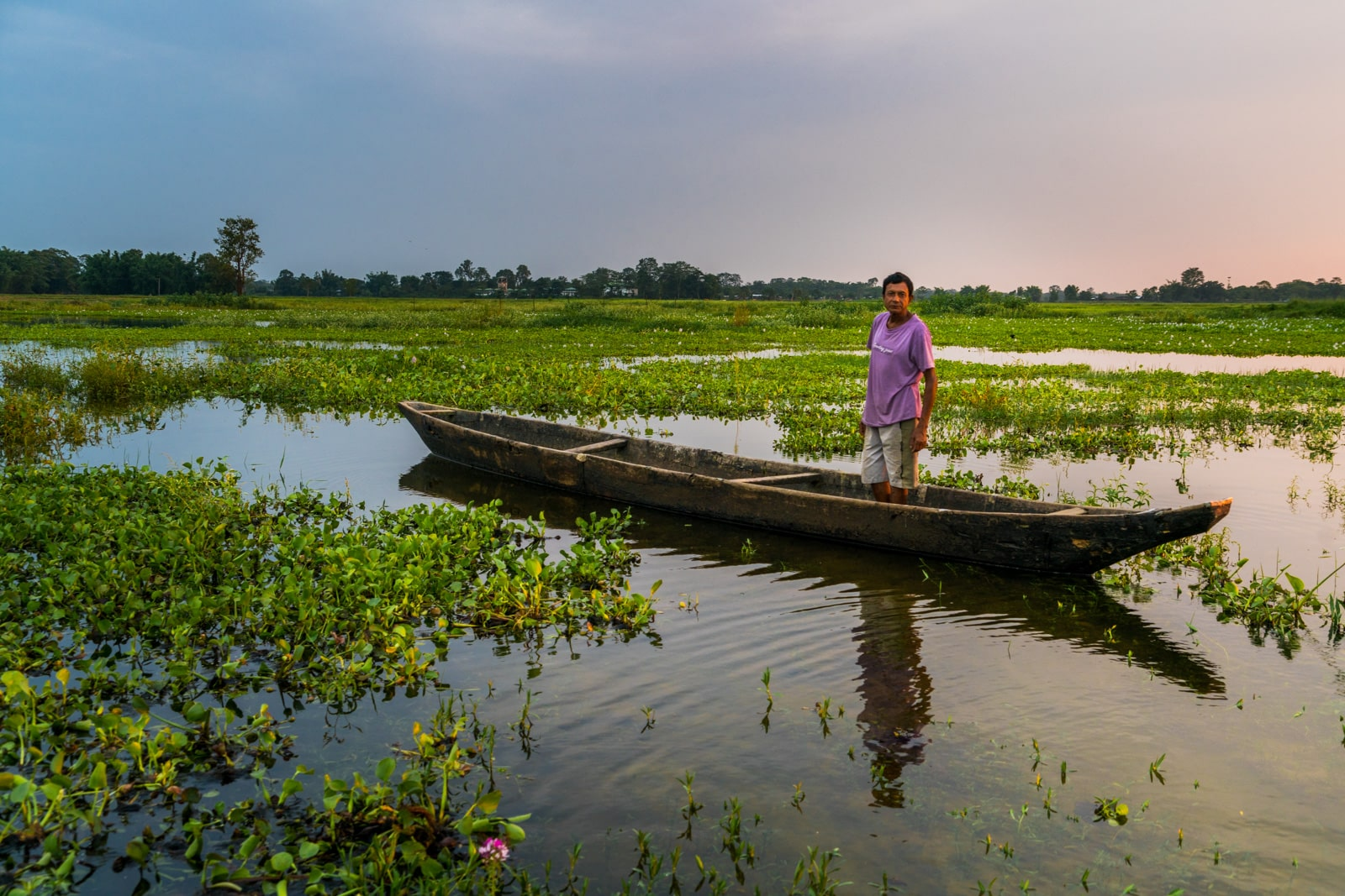 Local fisherman in a boat in Majuli river island in Assam, India - Lost With Purpose travel blog