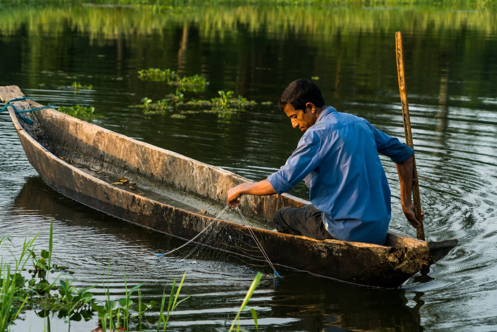 Fisherman in a boat checking nets in Majuli river island in Assam, India - Lost With Purpose travel blog