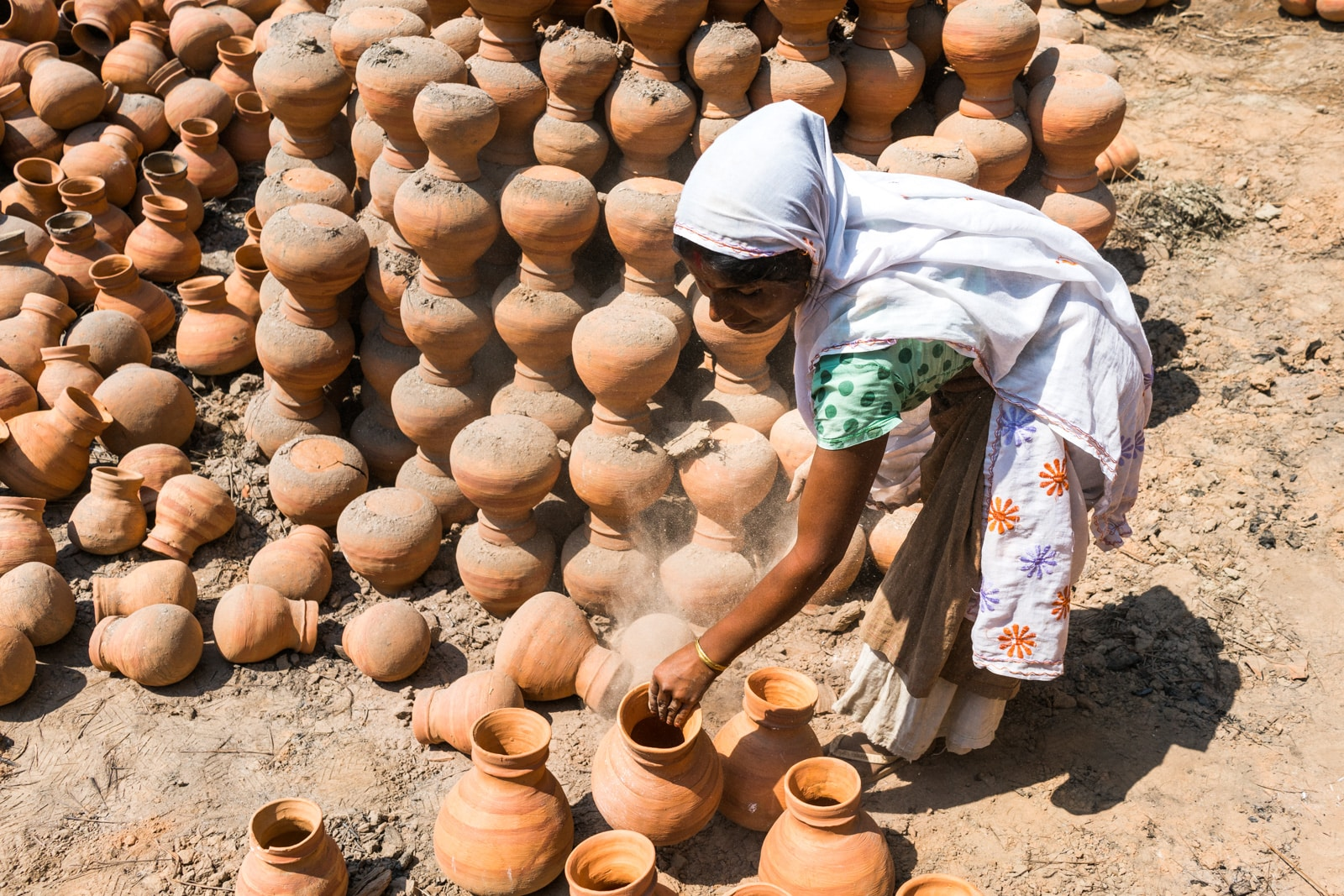 A Kumar woman making clay pots from mud