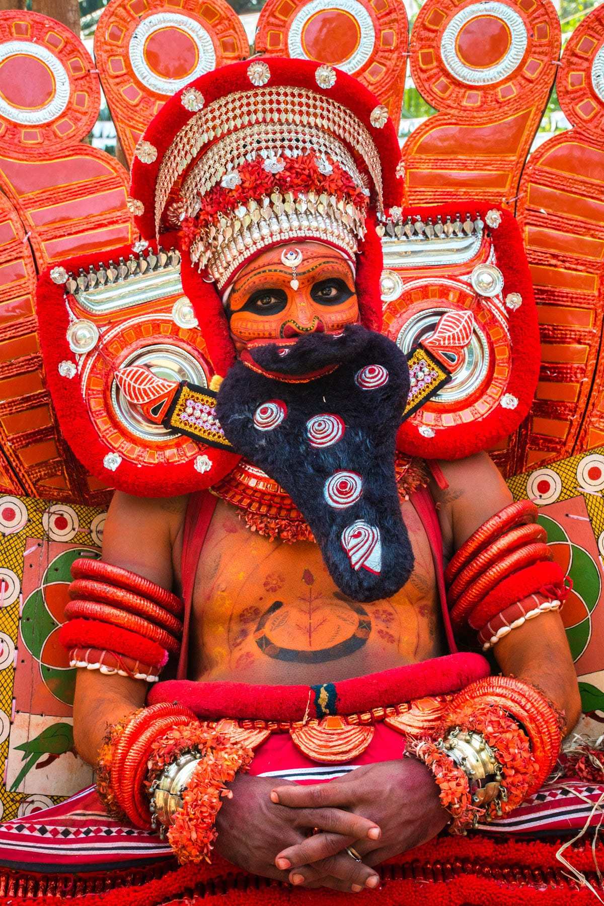 A Theyyam dancer catching his breath in Kannur, Kerala, a great off the beaten track activity in India.