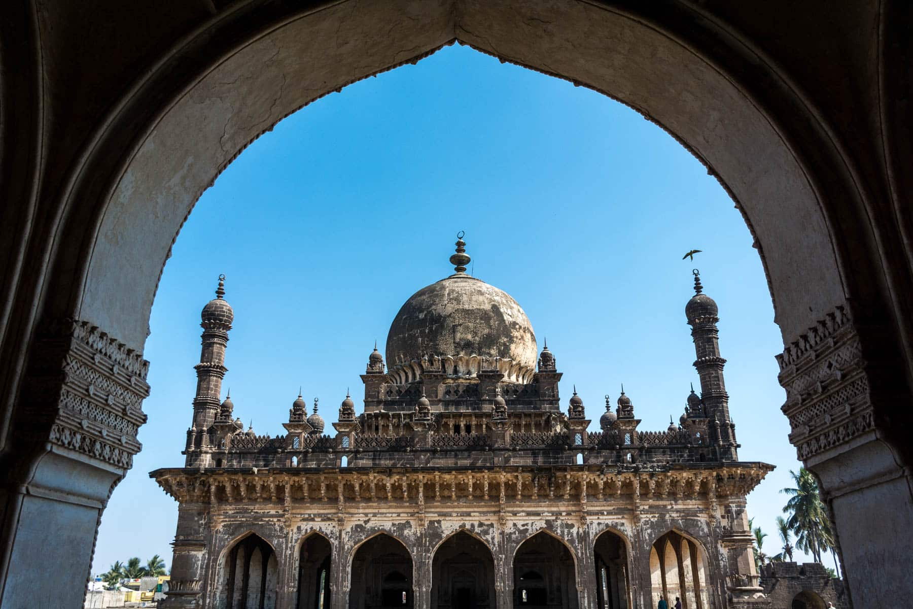 Best destinations off the beaten track in India - Ibrahim Rauza mausoleum through an archway in Bijapur, Karnataka - Lost With Purpose travel blog