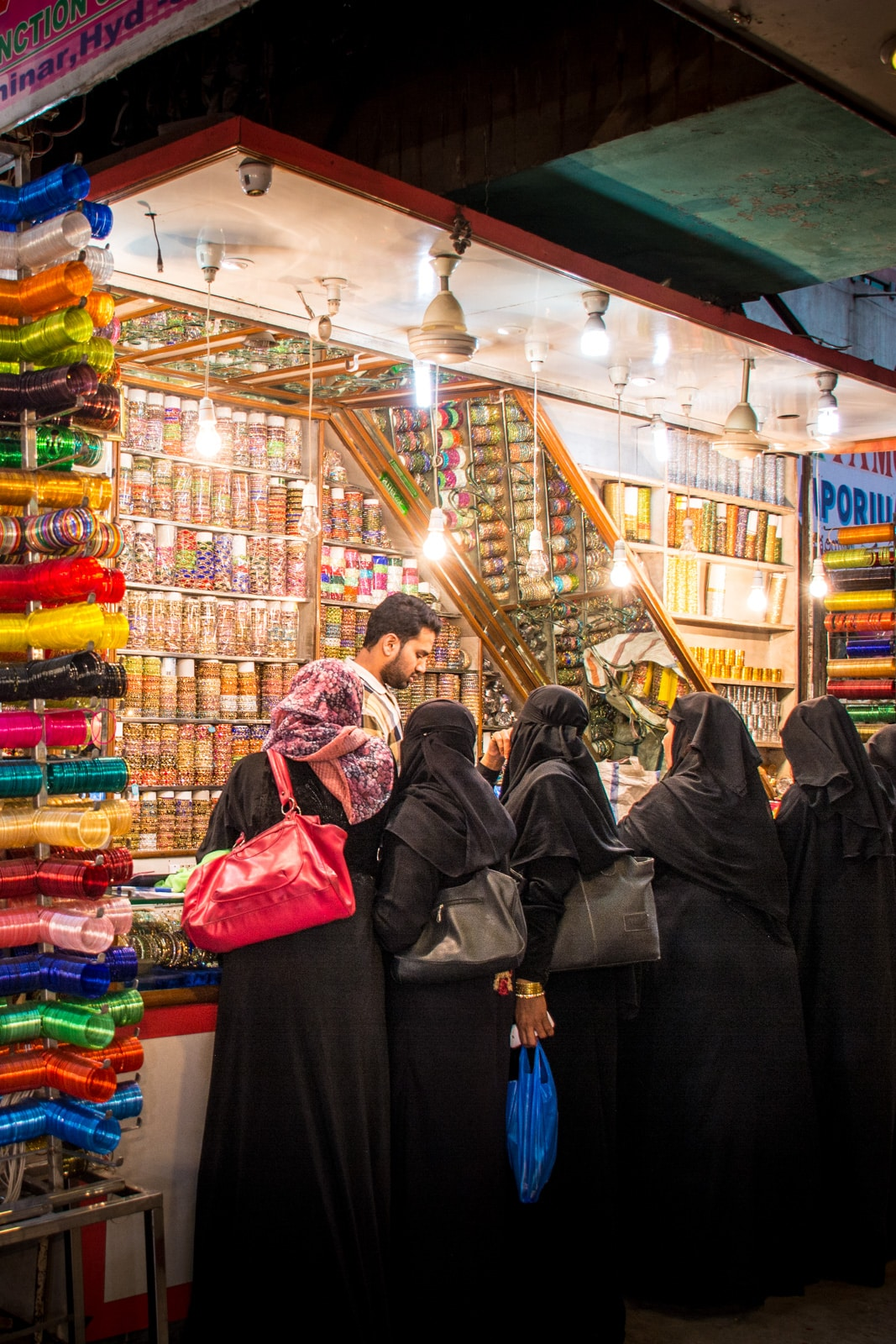 Women in black burqa buying bangles in one of many bazaars in the old city of Hyderabad, India, a great off the beaten track destination for adventurous and foodie travelers.