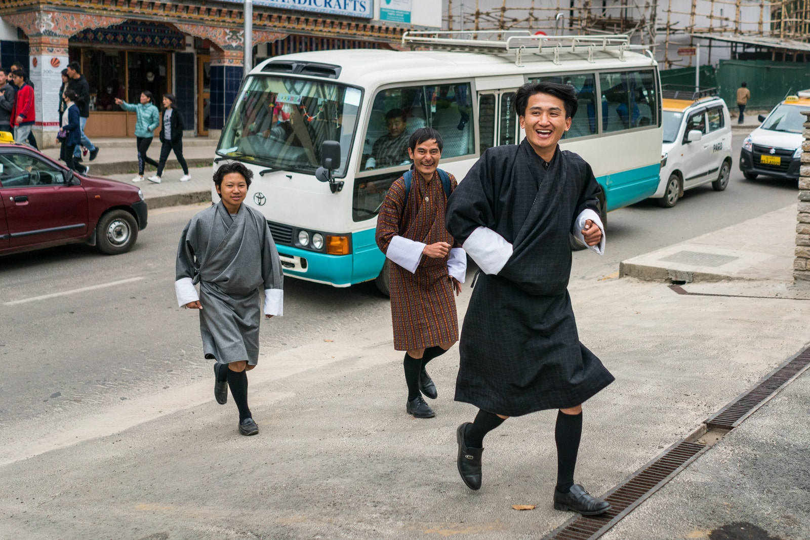 What it's like to go on a guided tour in Bhutan - Three tour guides walking on the streets of Thimphu - Lost With Purpose travel blog