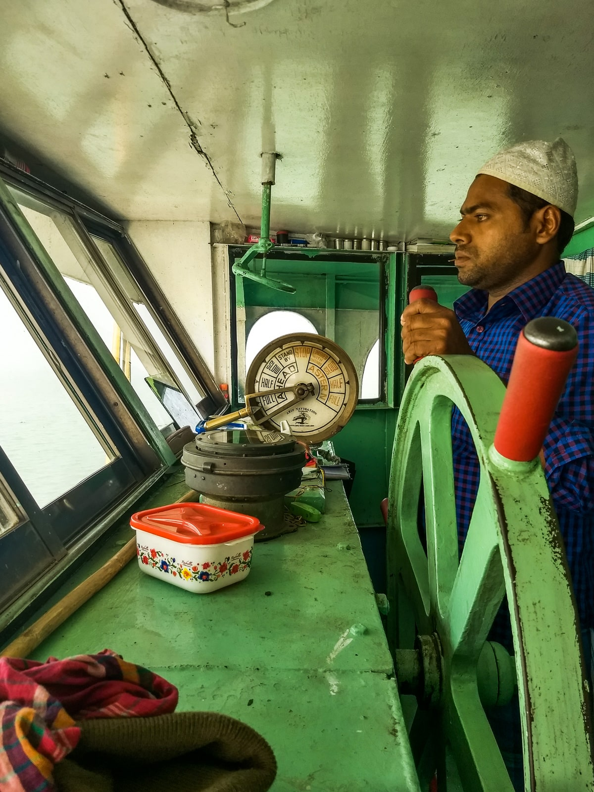 how to get from Chittagong to Barisal by boat in Bangladesh - Captain driving launch from Chittagong - Lost With Purpose travel blog