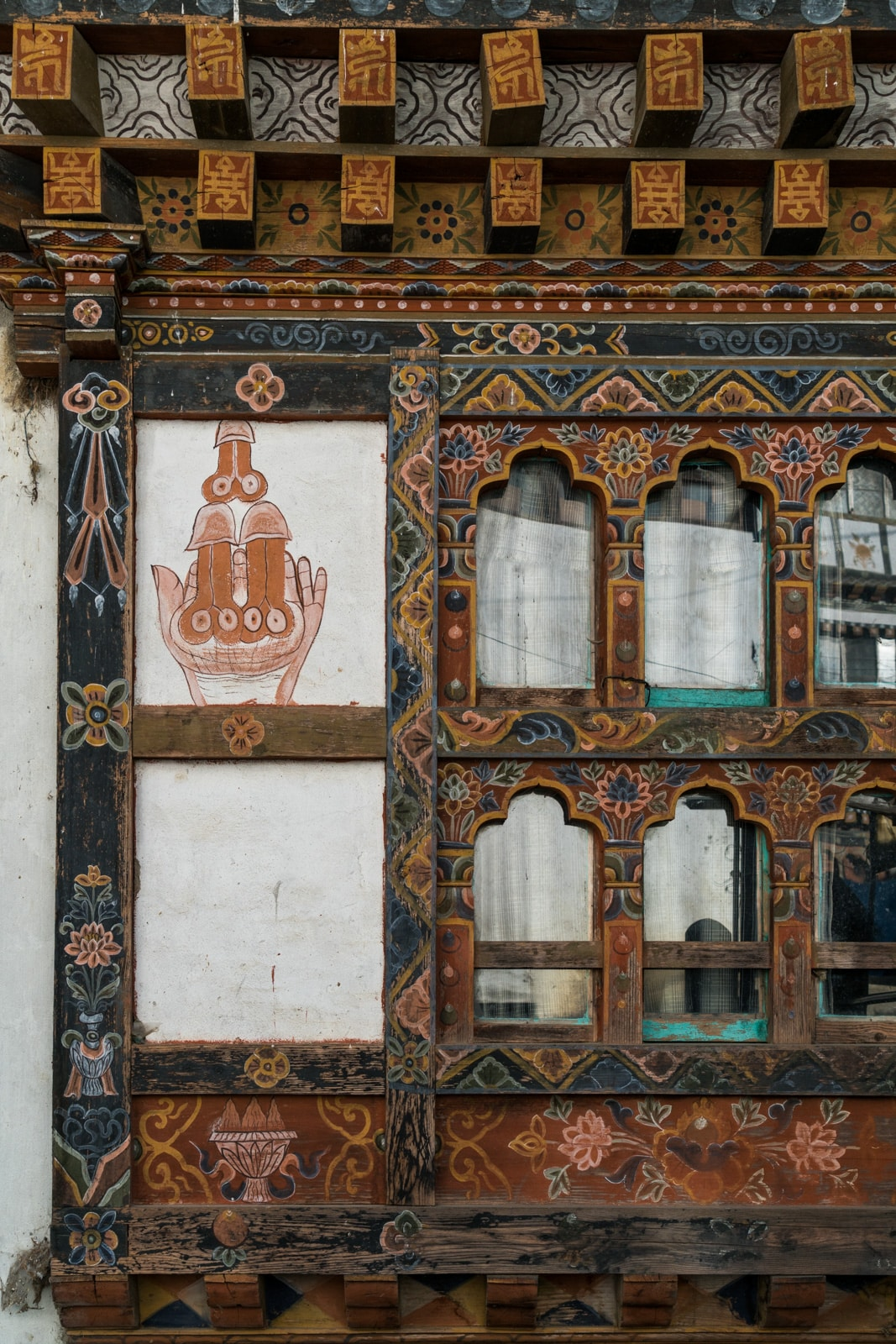 Several phalluses painted on the side of a traditional Bhutanese house.