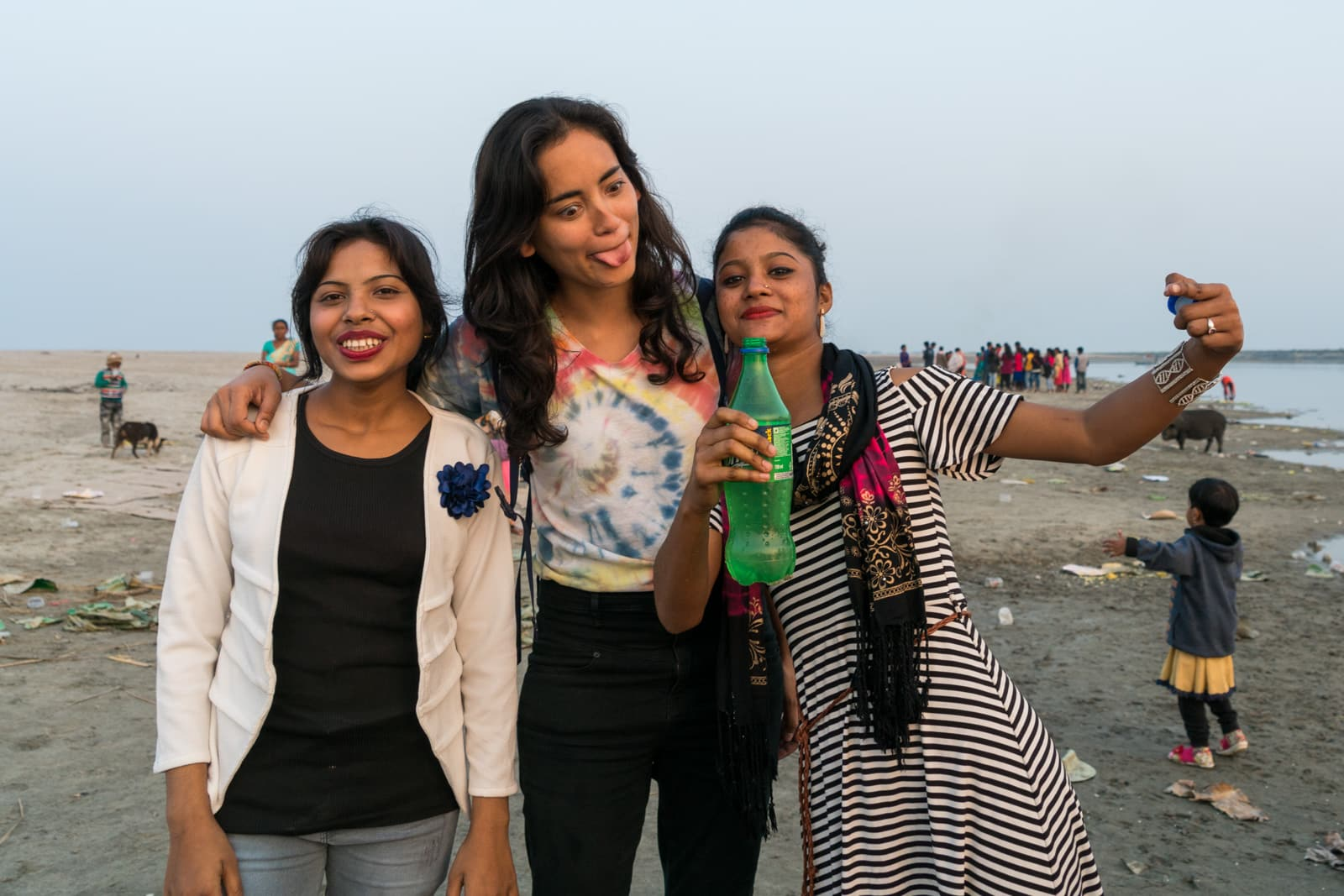 Going from couples travel to female solo travel - Alex with a family picnicking on Majuli island - Lost With Purpose travel blog