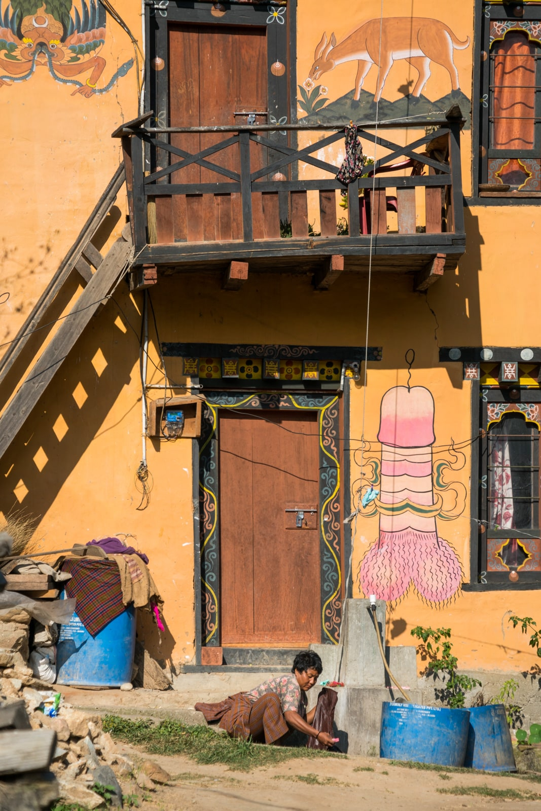A woman doing laundry in front of a house with a painted penis on it in Punakha, Bhutan.
