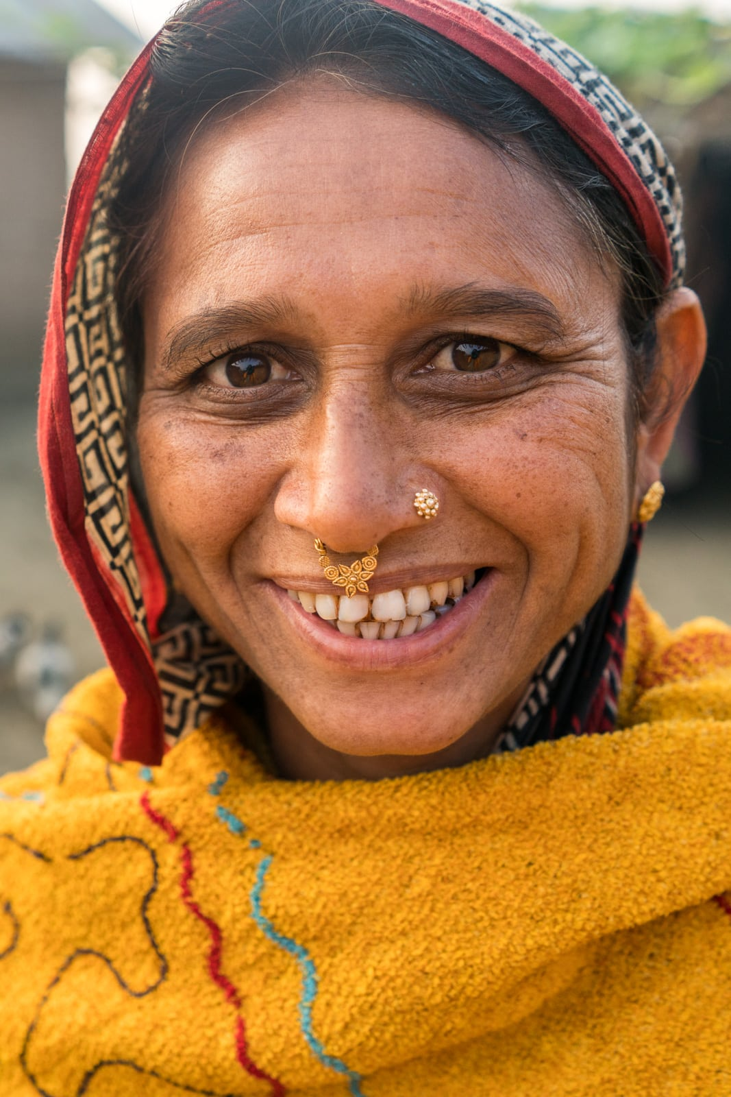 A smiling Bangladeshi woman in yellow headscarf in Assam, India.