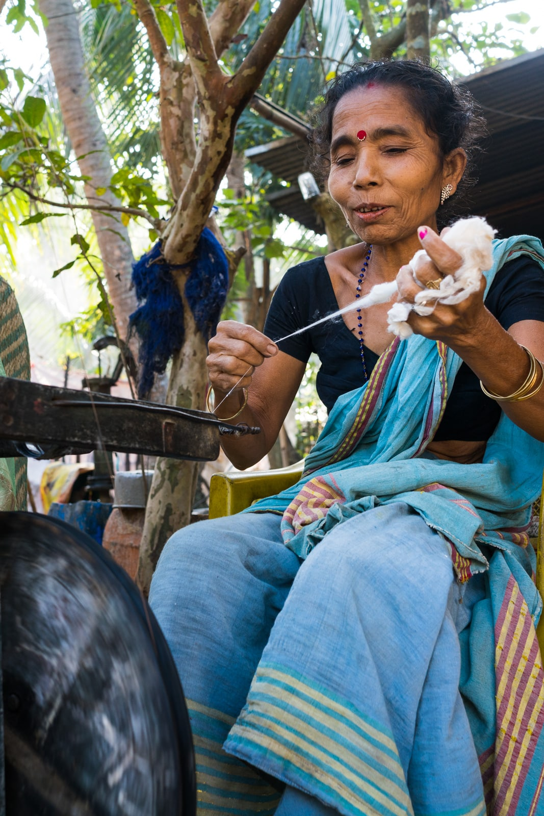 A local woman spinning thread in Assam, India.