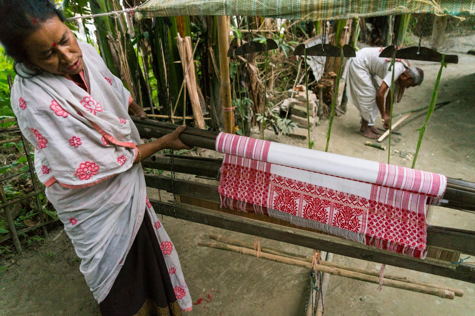 Luxury river cruise in India with Assam Bengal Navigation - Assamese woman showing off gamosa scarf weaving on a loom - Lost With Purpose travel blog
