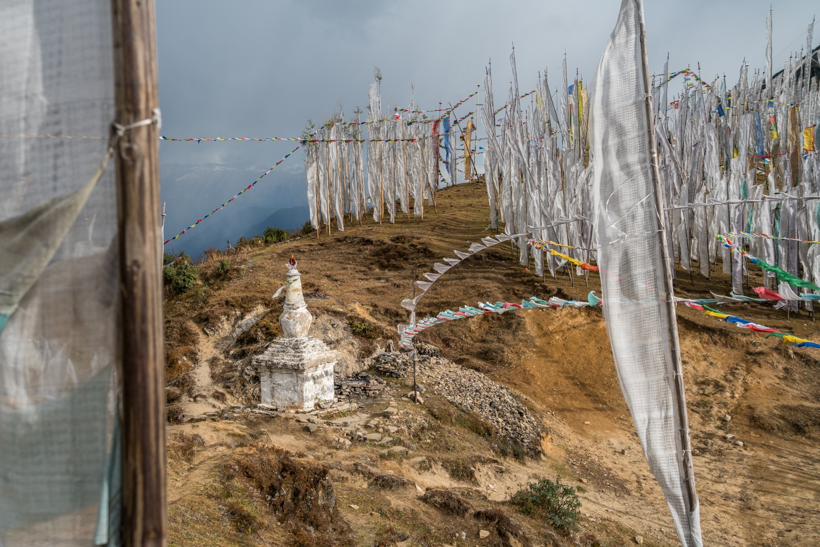 Is Bhutan worth the money - White prayer flags and a small stupa on Chele La mountain pass - Lost With Purpose travel blog