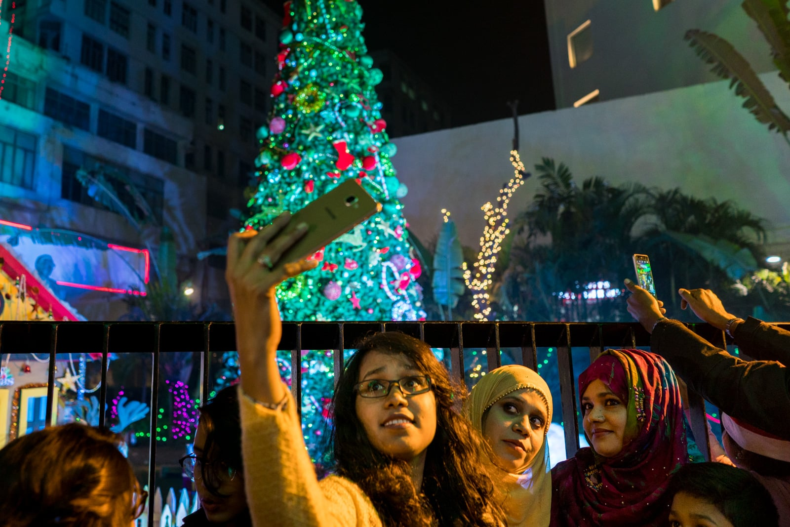 Christmas in Kolkata, India - Girls in hijab taking selfies in front of a Christmas tree on Park Street - Lost With Purpose travel blog