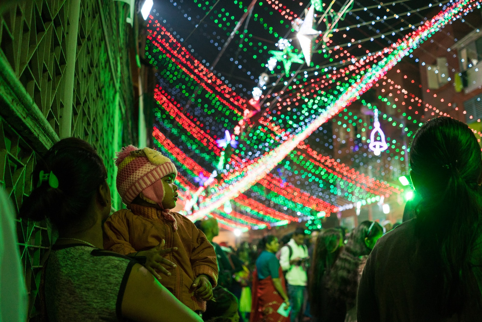 Celebrating Christmas in Kolkata, India - A child looking at Christmas lights in Barracks on Christmas Eve - Lost With Purpose travel blog