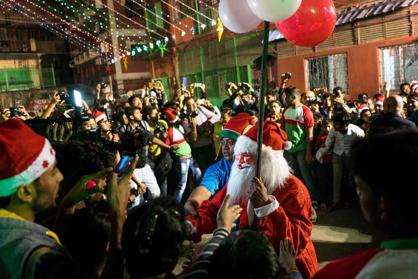 Celebrating Christmas in Kolkata, India - Elf pushing Santa in the crowd at Barracks - Lost With Purpose travel blog