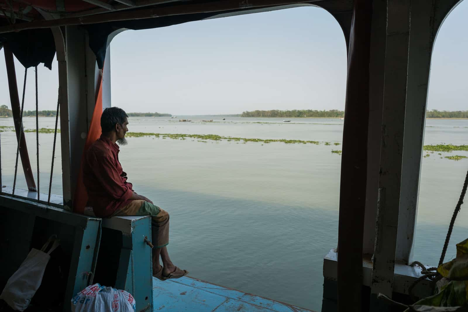 How to get a launch boat from Hularhat to Dhaka, Bangladesh - Man looking out over the Kaliganga river - Lost With Purpose travel blog