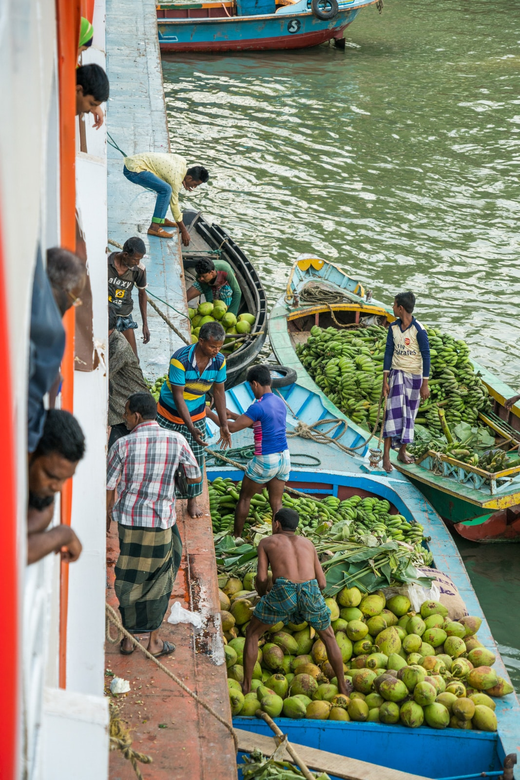 Several boats of men loading bananas and coconuts onto a launch boat in Bangladesh.