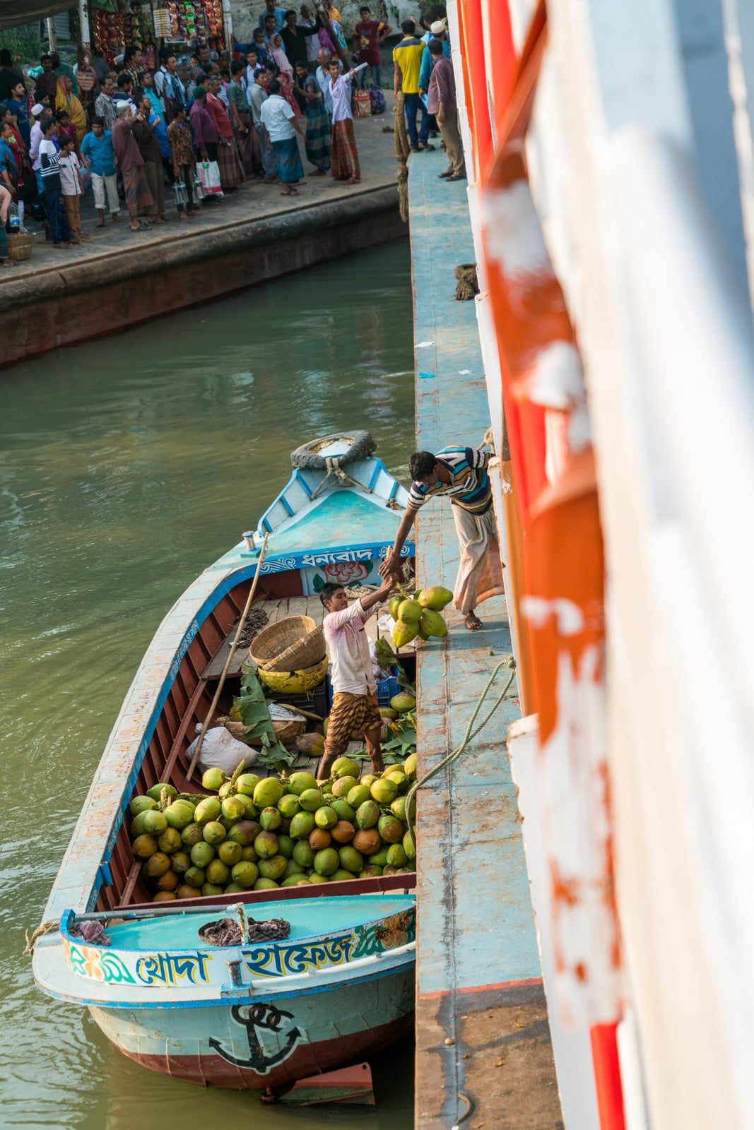 Men loading coconuts onto a launch ferry boat on the Kaliganga river in Bangladesh.