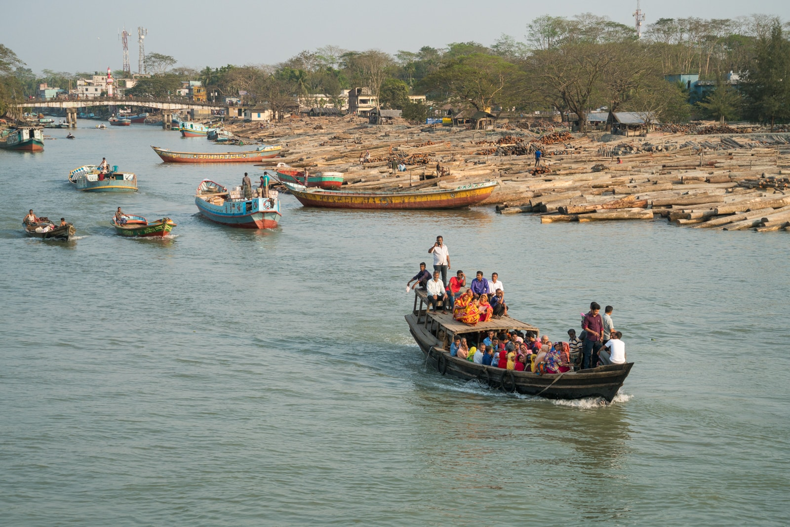 How to take a launch boat from Khulna to Dhaka via Hularhat, Bangladesh - Boats sailing through a lumber yard - Lost With Purpose travel blog