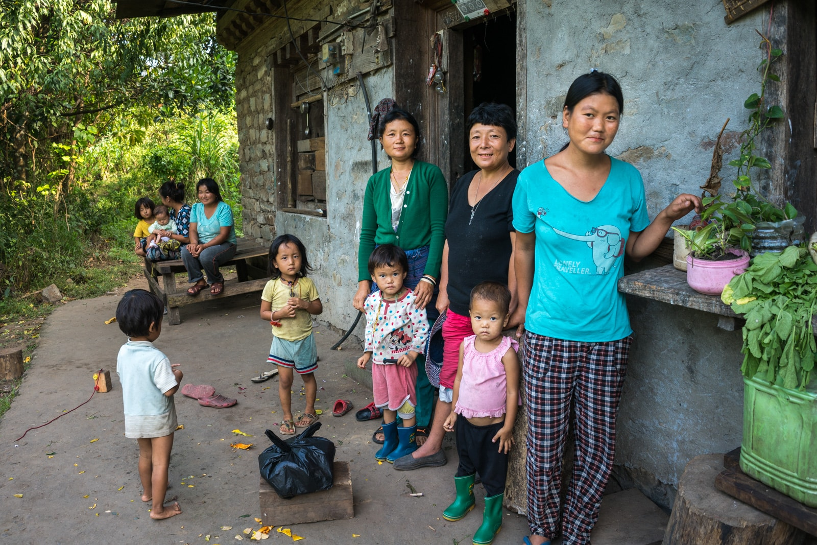 Traveling off the beaten track in Bhutan - A family standing outside a house in Birtii - Lost With Purpose travel blog